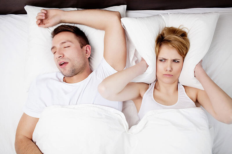 woman covering her ears with pillow because of snoring partner